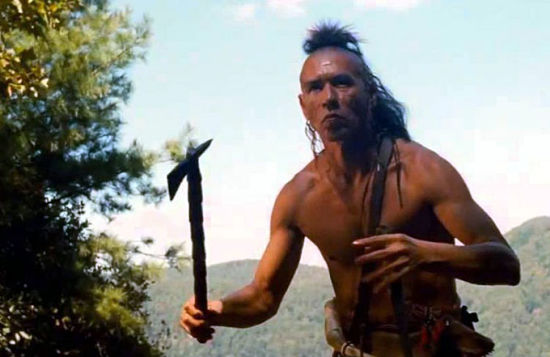 Wes Studi as Magua, holding a tomahawk