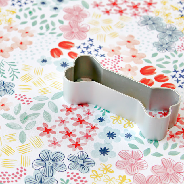 Bone shaped dog treat cookie cutter on a floral background