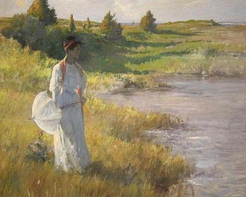 Woman in white dress and with umbrella is standing near the lake