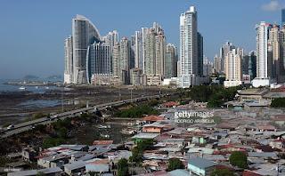 Φωτογραφία του Juan Jose Rodriguez για το πρακτορείο Getty, που δείχνει την ακραία αντίθεση της φτωχογειτονιάς (φαβέλας) Boca la Caja στην Πόλη του Παναμά (σε πρώτο επίπεδο) και της Punta Pacifica (στο βάθος) με τους εκατοντάδες υπερμοντέρνους ουρανοξύστες όπου εδρεύει και η περίφημη Γερμανο-Παναμέζικη νομική εταιρεία Mossack Fonseca. Η φωτογραφία συμβολίζει την απόλυτη ανισότητα (και διαφθορά) της νεοφιλελεύθερης παγκοσμιοποίησης εν έτει 2016 στον πλανήτη Γη και από μόνη της δείχνει όσα λένε χιλιάδες σελίδες των Panama Papers μαζί