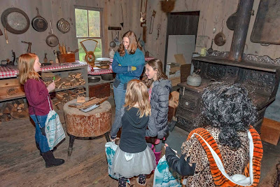 Children in Halloween costumes in kitchen of lumber camp with cast iron cook stove