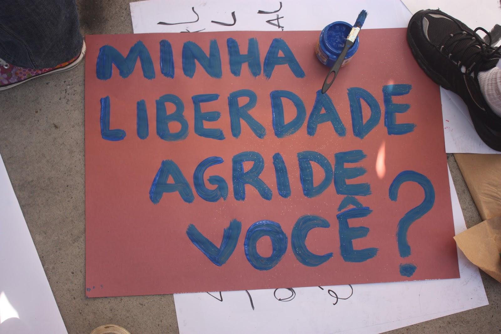 """Um cartaz de protesto onde está escrito """"Minha liberdade agride você?"""""""