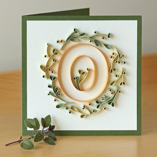 Quilled paper letter O surrounded by quilled leafy vine on greeting card