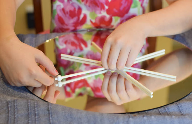 Winter STEM- Build A Snowflake Tinker Tray.  Use loose parts to build snowflakes.  Explore radial symmetry as you incorporate math, science, fine motor work, and creativity in this activity for preschoolers, kindergartners, and elementary school.