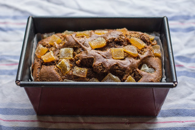 The spicy ginger cake baked and still in the baking tin on a striped tea towel