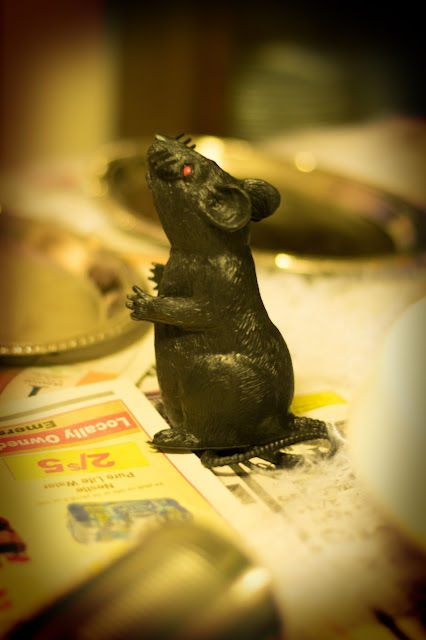 A picture of a plastic rat on the table.