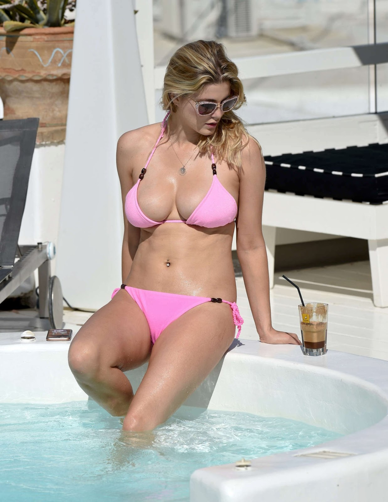 Ashley James gives a busty poolside appearance in Greece