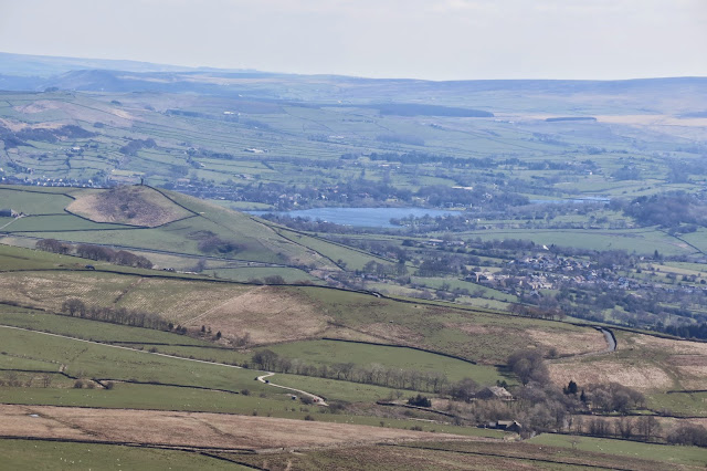 A view of farmland and villages from Pendle Hill with a small tower on a hill to the left.