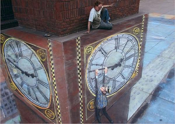 Bir saat kulesinin yelkovanına asılı duran bir adamı gösteren kaldırım sanatı resmi