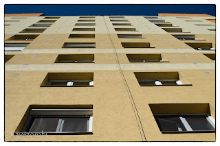 Panelház ablakai felfele nézve kék éggel