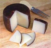 a photo of a wheel abd slices of Murcia Al Vino cheese