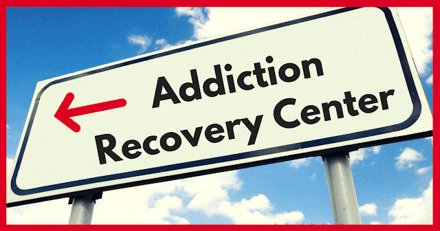 "A highway sign, set against a vibrant and cloudy sky, that says ""Addiction Recovery Center"" with a red arrow pointing to the left."