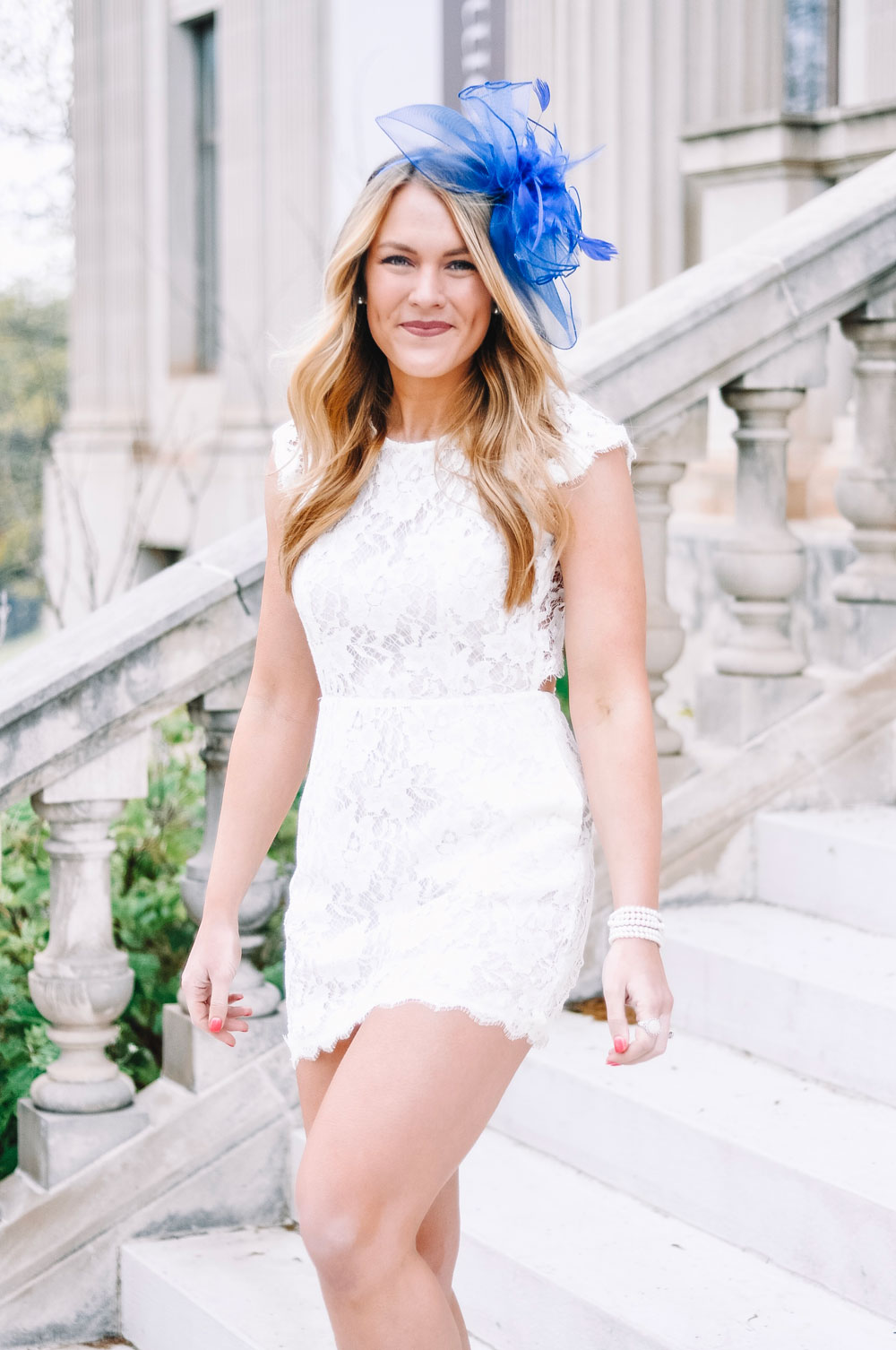 white lace dress and blue fascinator