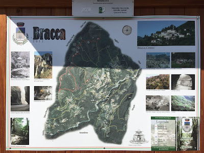Information board showing different hiking routes around Bracca including CAI (red) and local (yellow) trails.