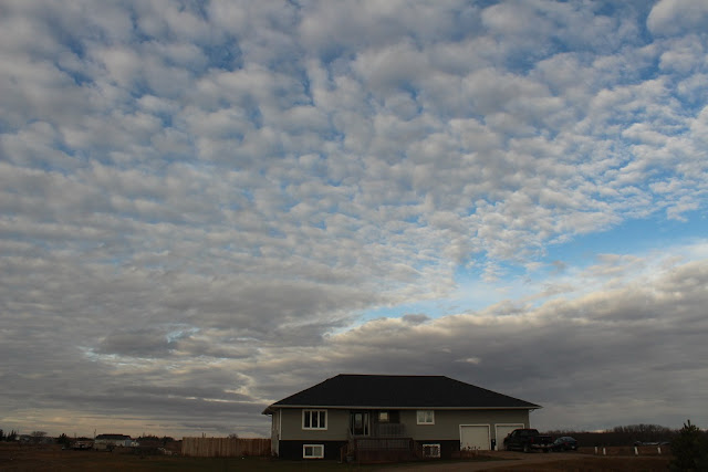 fluffy clouds over house