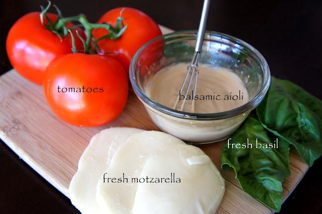 A display of needed ingredients for the Turkey Caprese Panini, tomatoes, balsamic aioli, fresh mozzarella and fresh basil