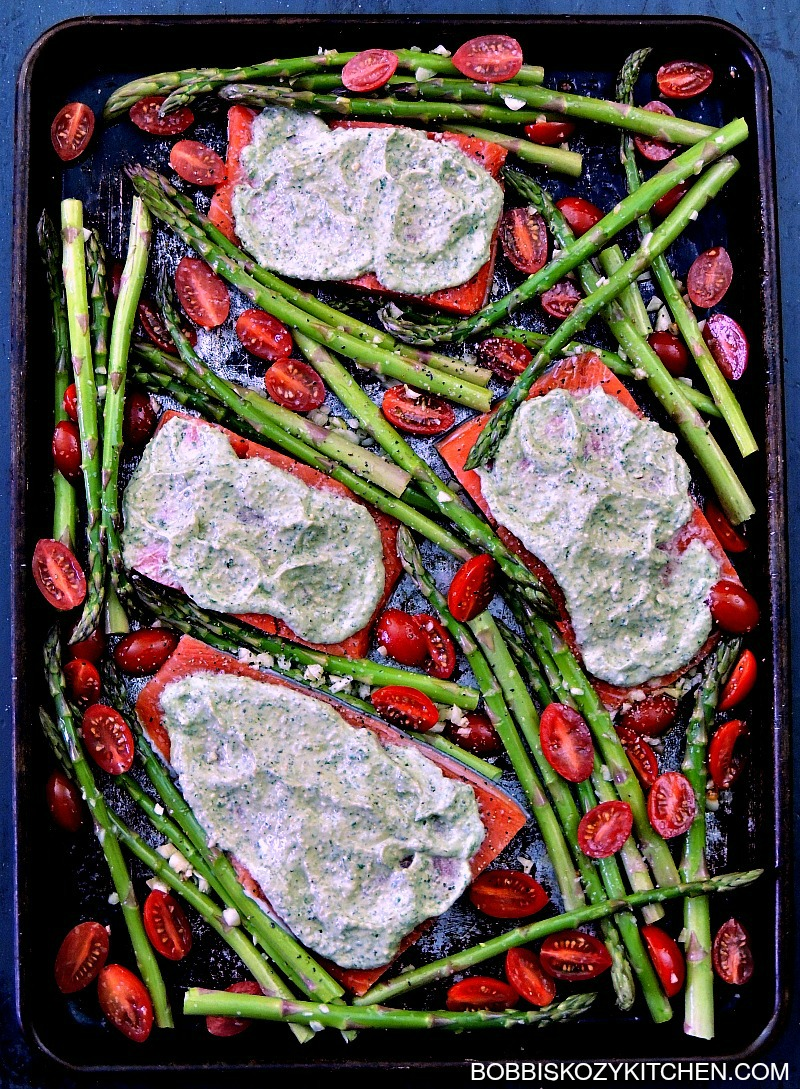 This Sheet Pan Pesto Salmon with Asparagus and Tomatoes recipe super easy, and done in less than 30 minutes, but doesn't scrimp on taste. A perfect weekday supper the whole family will love. #keto #lowcarb #sheetpan #onepot #onepan #30minuterecipe #easy #salmon #pesto #asparagus #tomatoes #recipe |   bobbiskozykitchen.com