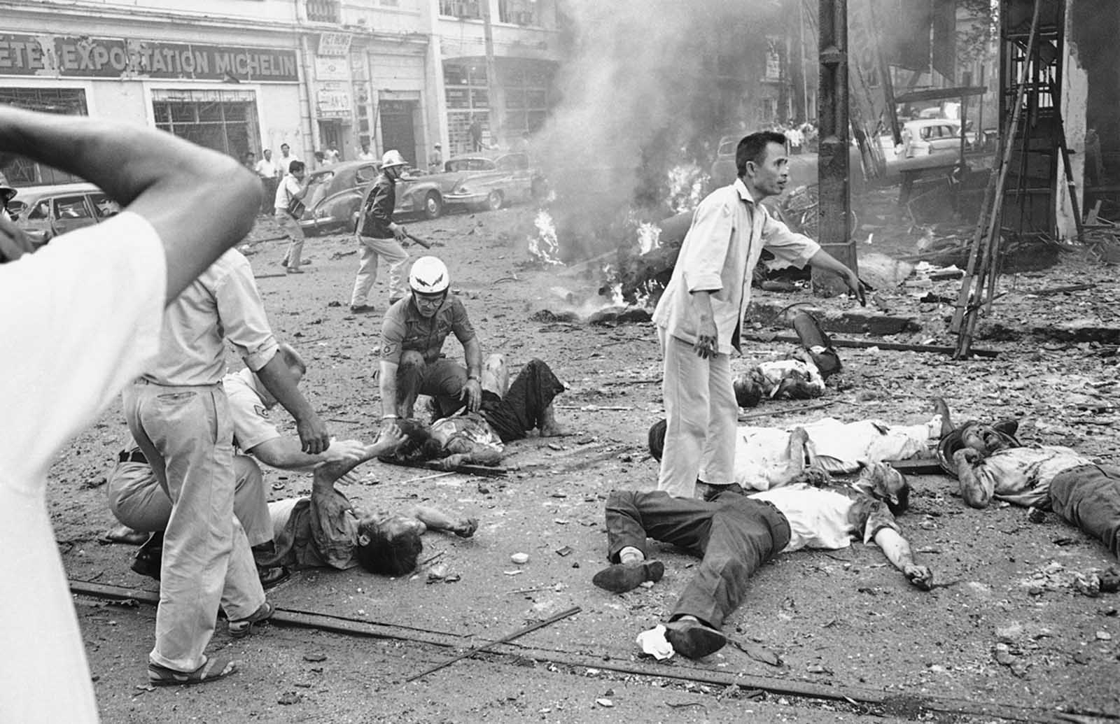 Injured Vietnamese receive aid as they lie on the street after a bomb explosion outside the U.S. embassy in Saigon, Vietnam, on March 30, 1965. Smoke rises from wreckage in background. At least two Americans and several Vietnamese were killed in the bombing.