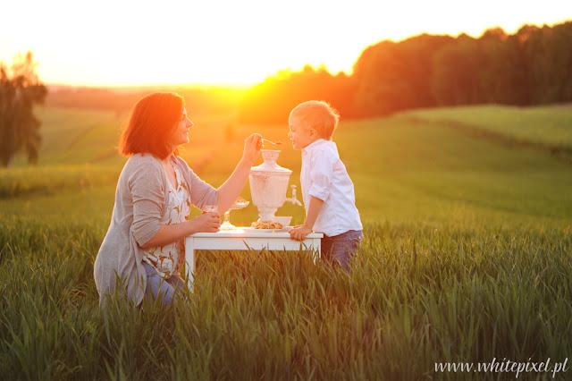 Mama z synem na sesji w plenerze bawią się, grają i czytają książkę