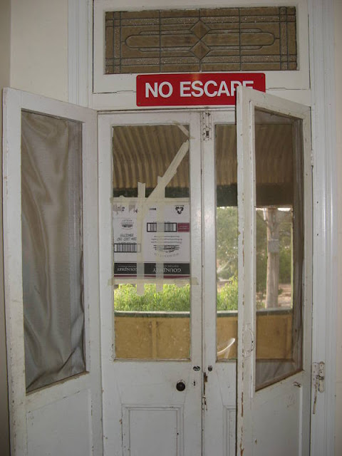 "door to a balcony with ""no escape"" sign"