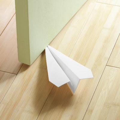 Avión con apariencia de papel para mantener abierta la puerta.