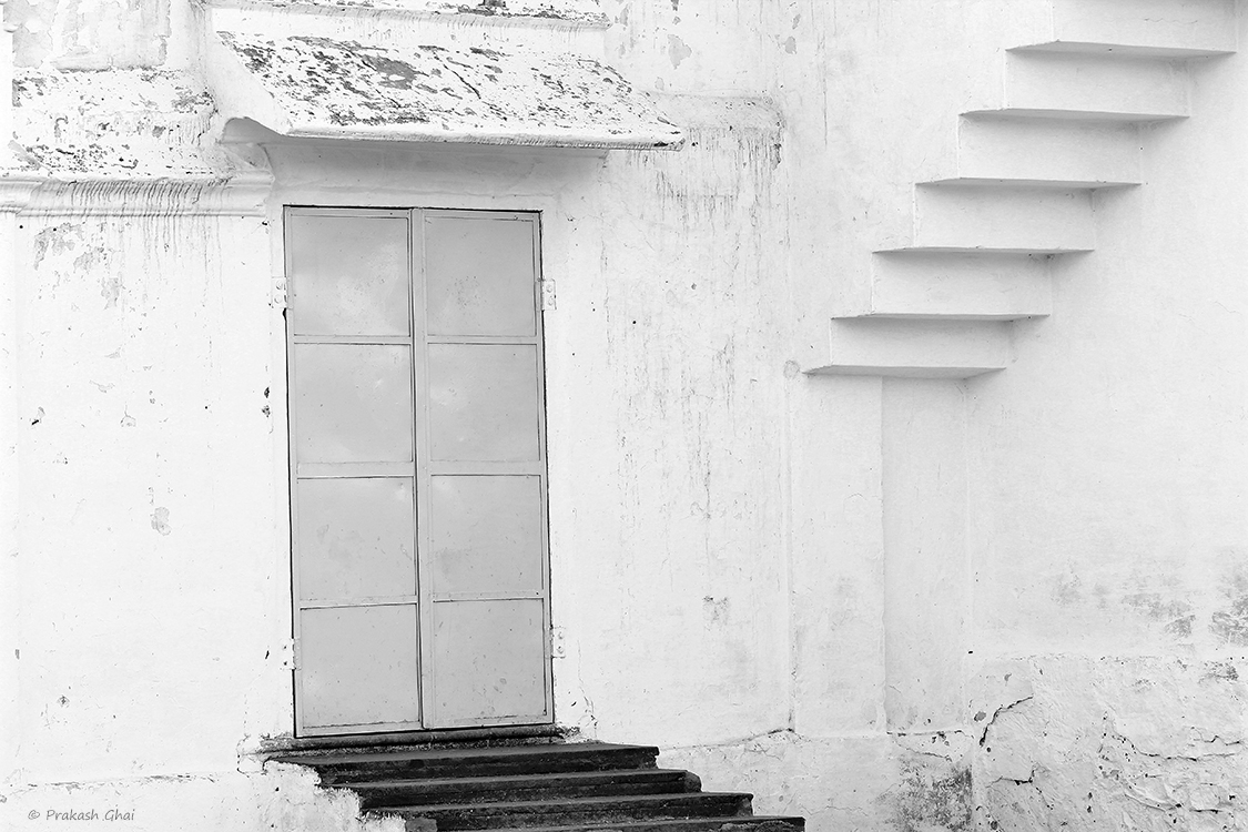 A Black and white Minimalist Photo of Steps leading to a closed door on the street right outside the Jharkhand Mahadev Temple in Vaishali Nagar Jaipur.