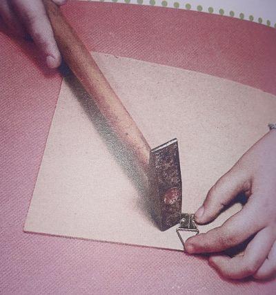 Mano clavando ganchito en el reverso de una madera o cuadro