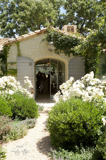 Front door to spanish style Patina Farm with flowers