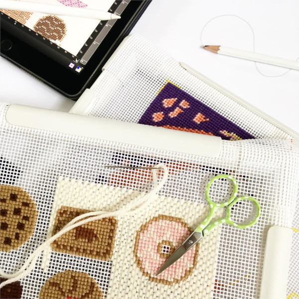 Needlepoint work in progress of biscuits including chocolate chip cookies and party rings