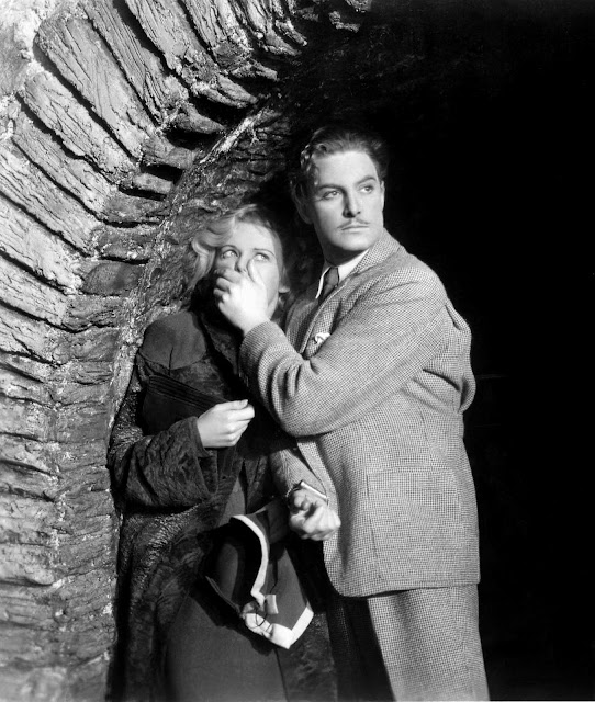Robert Donat and Madeleine Carroll hide under a bridge