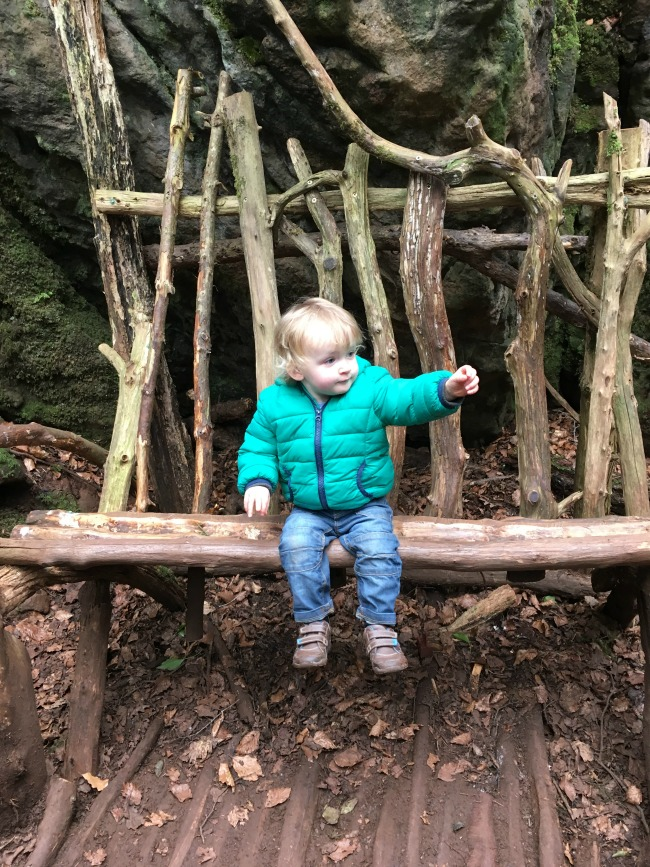 toddler sat on a bench made from sticks