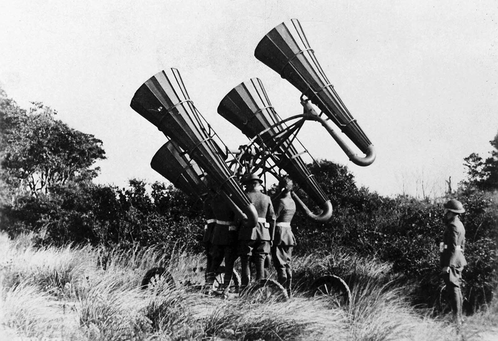 American troops using a newly-developed acoustic locator, mounted on a wheeled platform. The large horns amplified distant sounds, monitored through headphones worn by a crew member, who could direct the platform to move and pinpoint distant enemy aircraft. Development of passive acoustic location accelerated during World War I, later surpassed by the development of radar in the 1940s.
