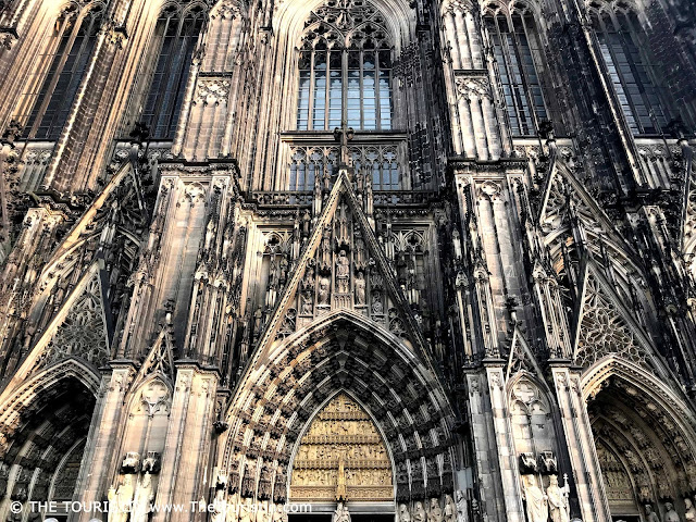 The facade of an elaborately decorated stone cathedral.