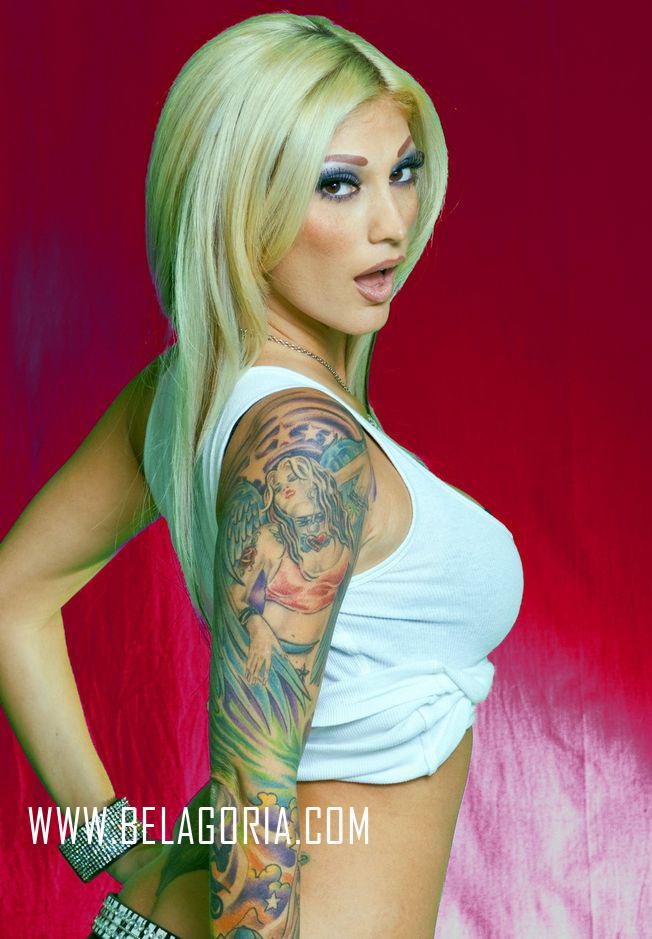 vemos a una mujer rubia que se gira sorprendida, lleva en su brazo derecho tatuaje a color, el tatuaje es de angel