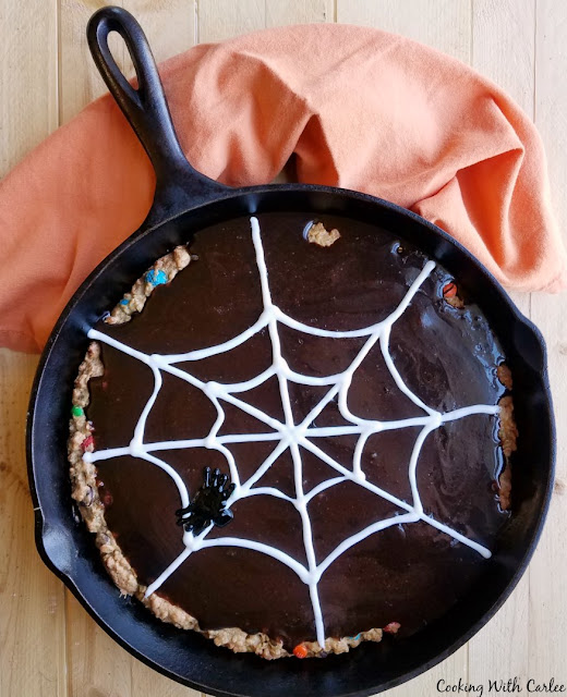 monster skillet cookie with rich chocolate frosting and icing spiderweb on top