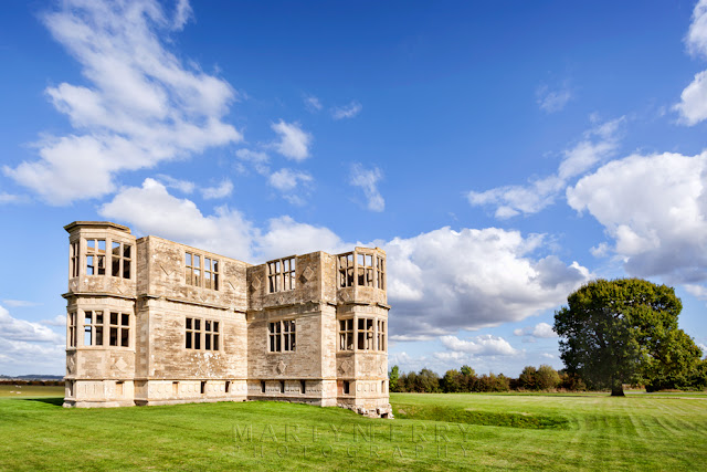 Lyveden New Bield in Northamptonshire under white clouds and a blue sky