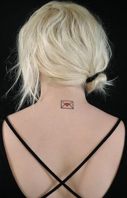 mujer rubia de espadas a nosotros, lleva el pelo recogido y apreciamos en su cuello el tatuaje de un sobre