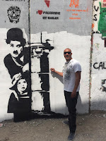 Yemen Elabed with a graffiti of charlie chaplin on the wall