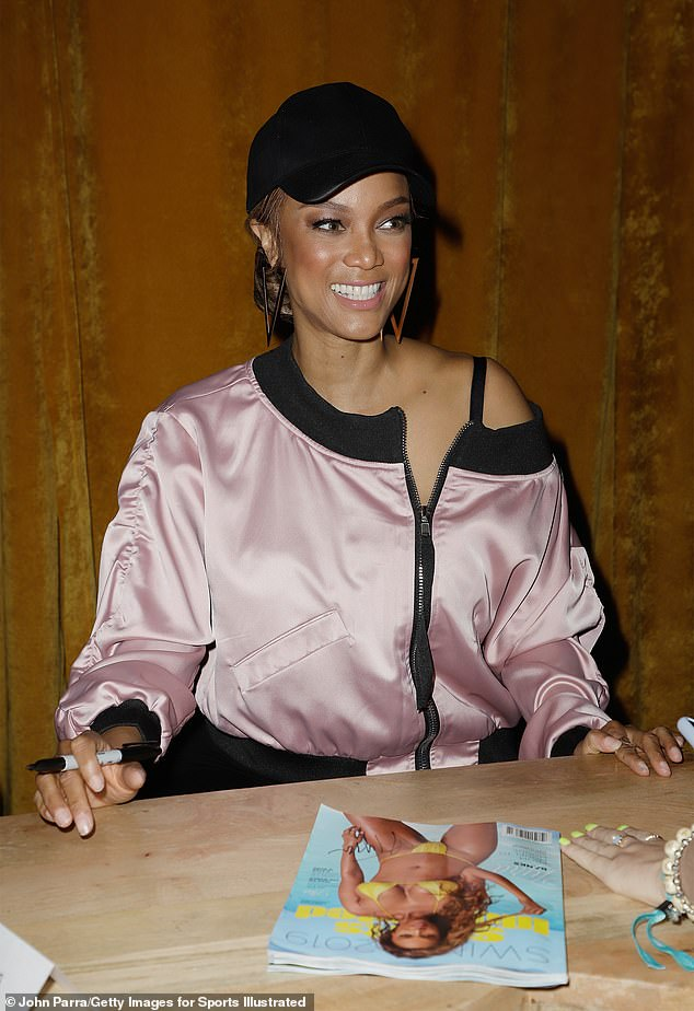 Tyra Banks flashes a megawatt smile as she steps out wearing black skinny jeans and a pink jacket