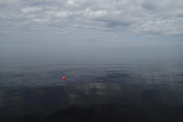 Tyyni meri ja pilvinen taivas, yksinäinen poiju kelluu keskellä kuvaa.