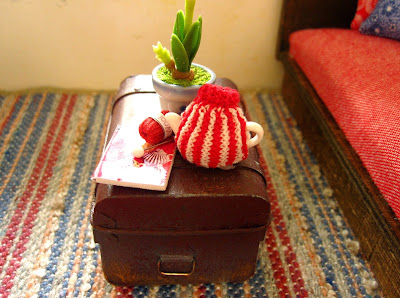 Modern dolls' house miniature stripy blue, fawn and red rug with trunk coffee table on top.