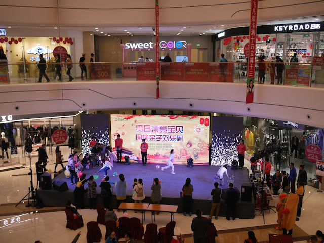 children competing in a game on a stage inside the Mudanjiang Wanda Plaza