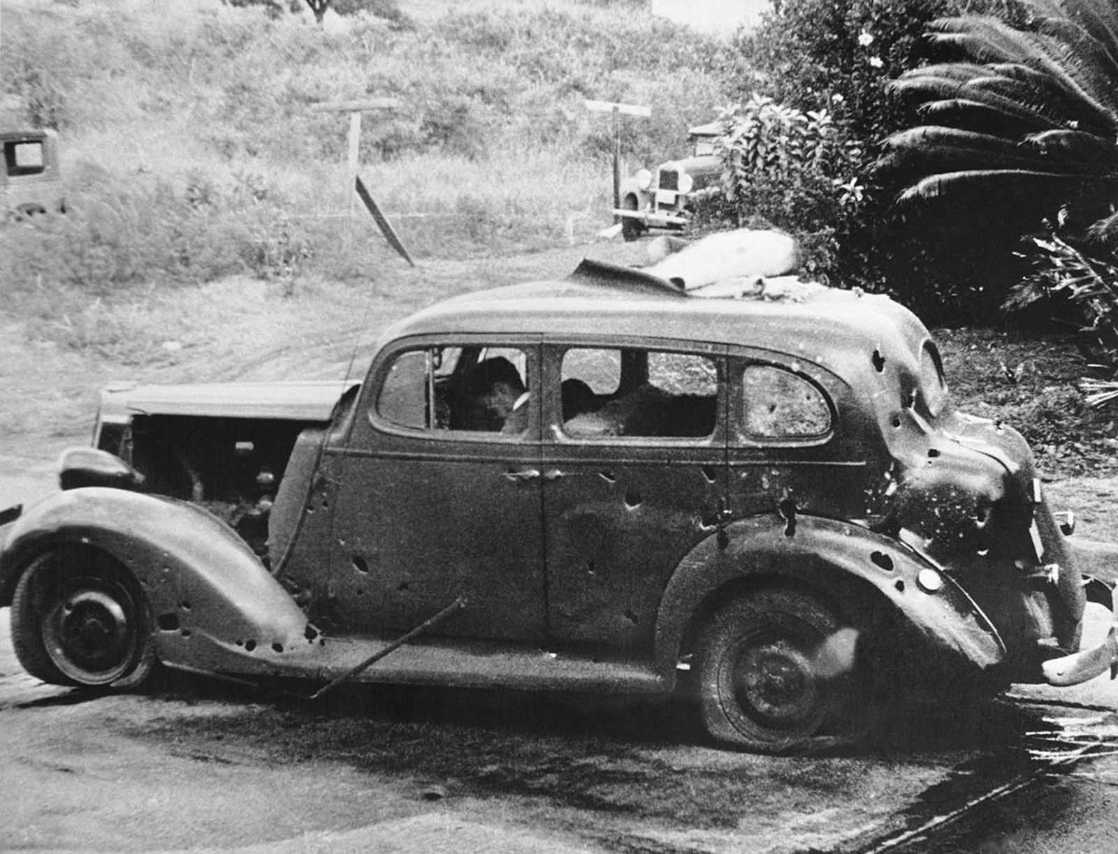 In this photo provided by the U.S. Navy, eight miles from Pearl Harbor, shrapnel from a Japanese bomb riddled this car and killed three civilians in the attack of December 7, 1941. Two of the victims can be seen in the front seat. The Navy reported there was no nearby military target.