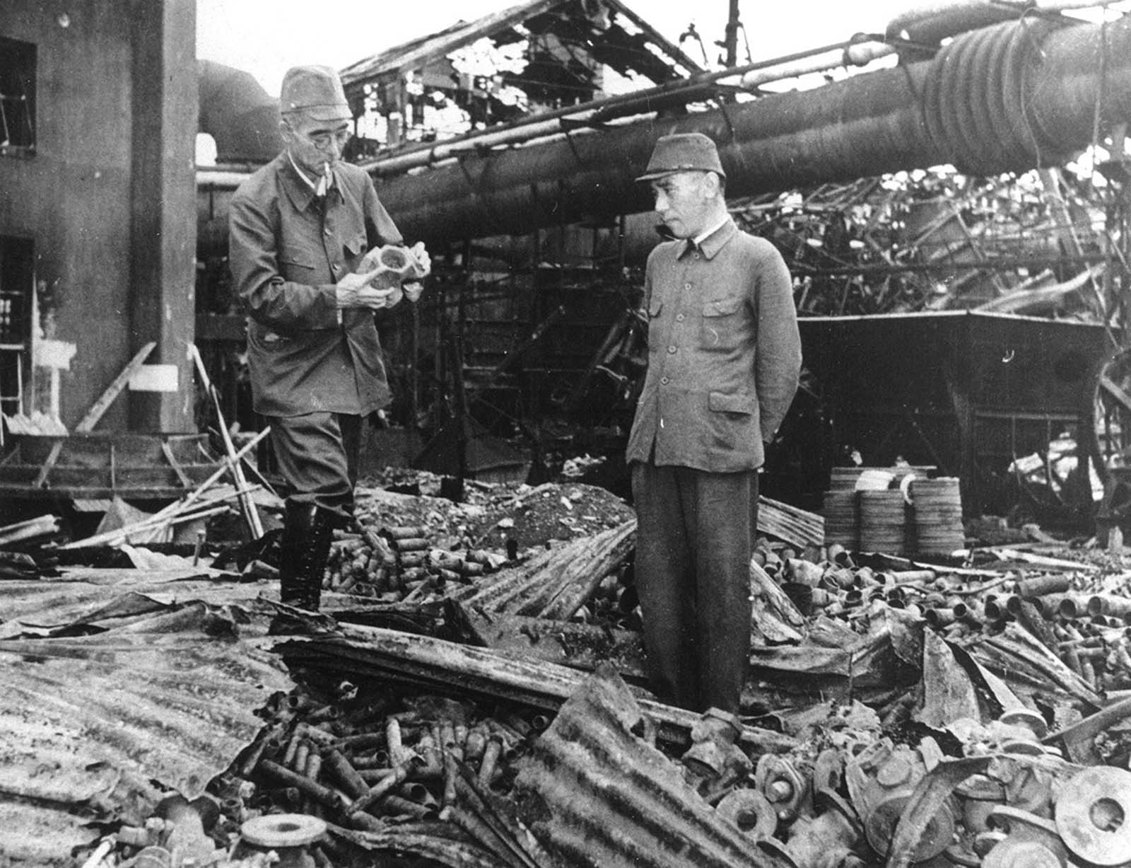 Ryozo Asano, left, spokesman for a group of diversified Japanese family enterprises called the Zaibatsu, inspects the wreckage of his steel plant in Tokyo, after the first U.S. air raid on Japan's capital, April 18, 1942. He is accompanied by an unidentified aide. Thirteen targets were struck, including an oil tank farm, a steel mill, and an aircraft carrier under construction. Some 50 Japanese lost their lives.
