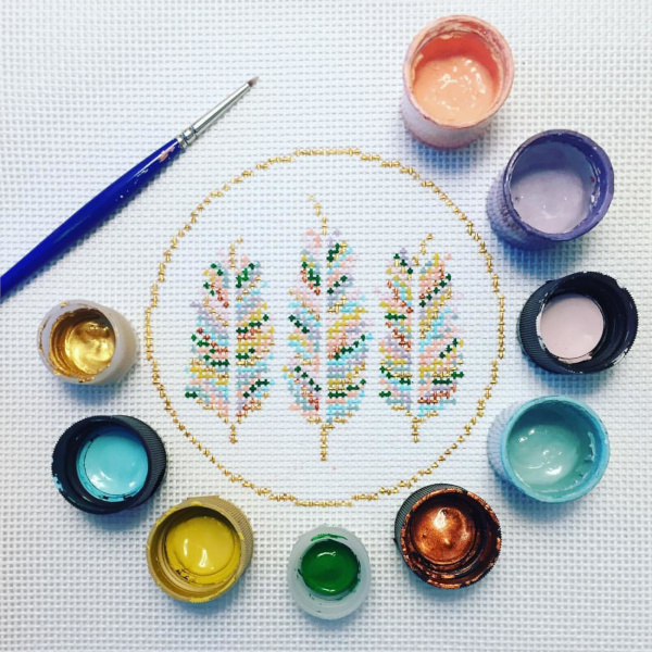 Three feathers in a circle of paint pots - painted onto needlepoint canvas