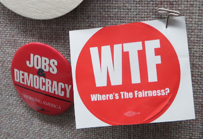 Red round sticker pinned to a bulletin board, reads WTF (Where's the Fairness?)