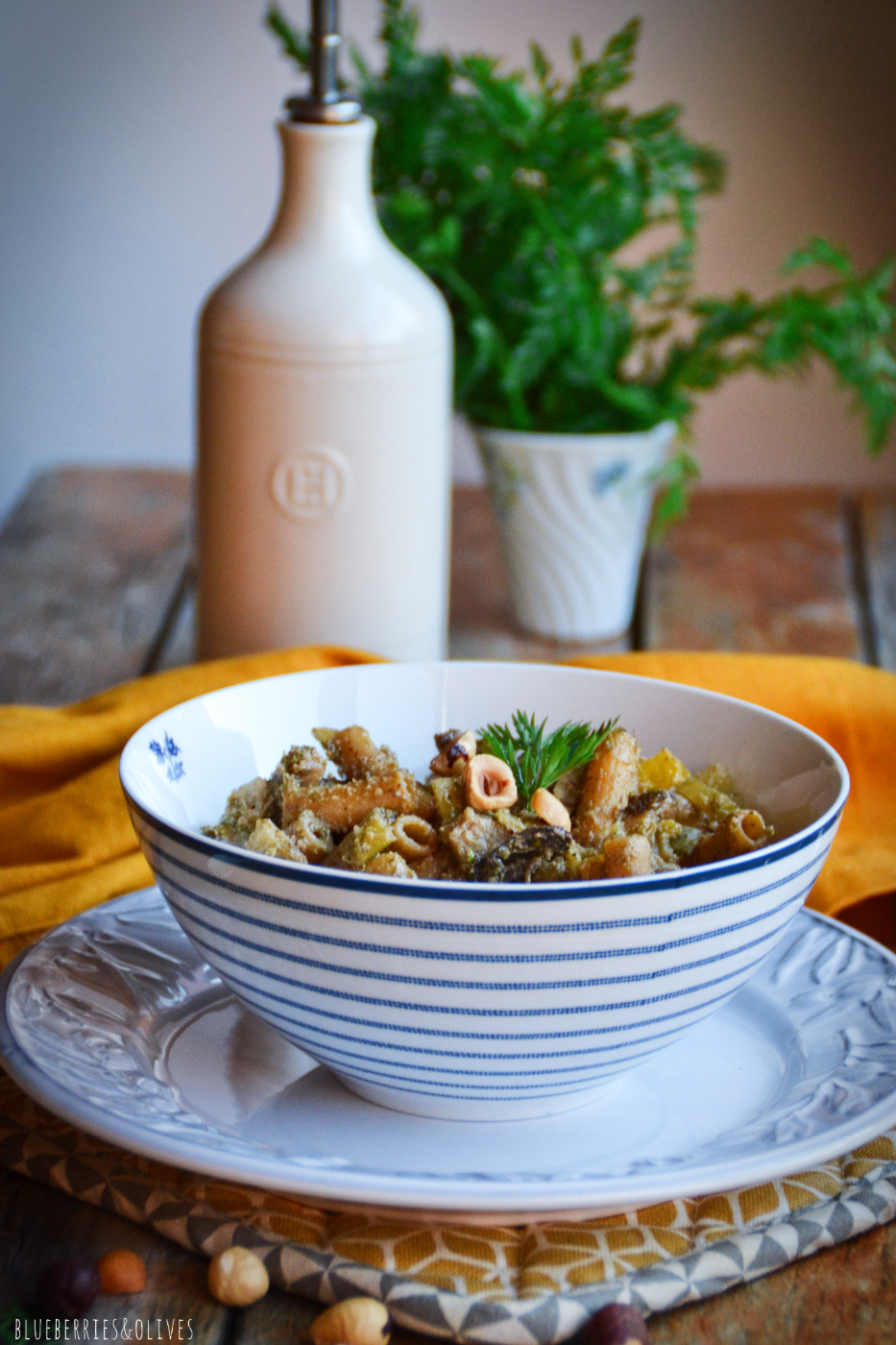 WHITE AND BLUE BOWL OF PASTA WITH FENNEL PESTO AND OLD WOODEN BACKGROUND, YELLOW TABLECLOTH, BOTTLE OF OLIVE OIL