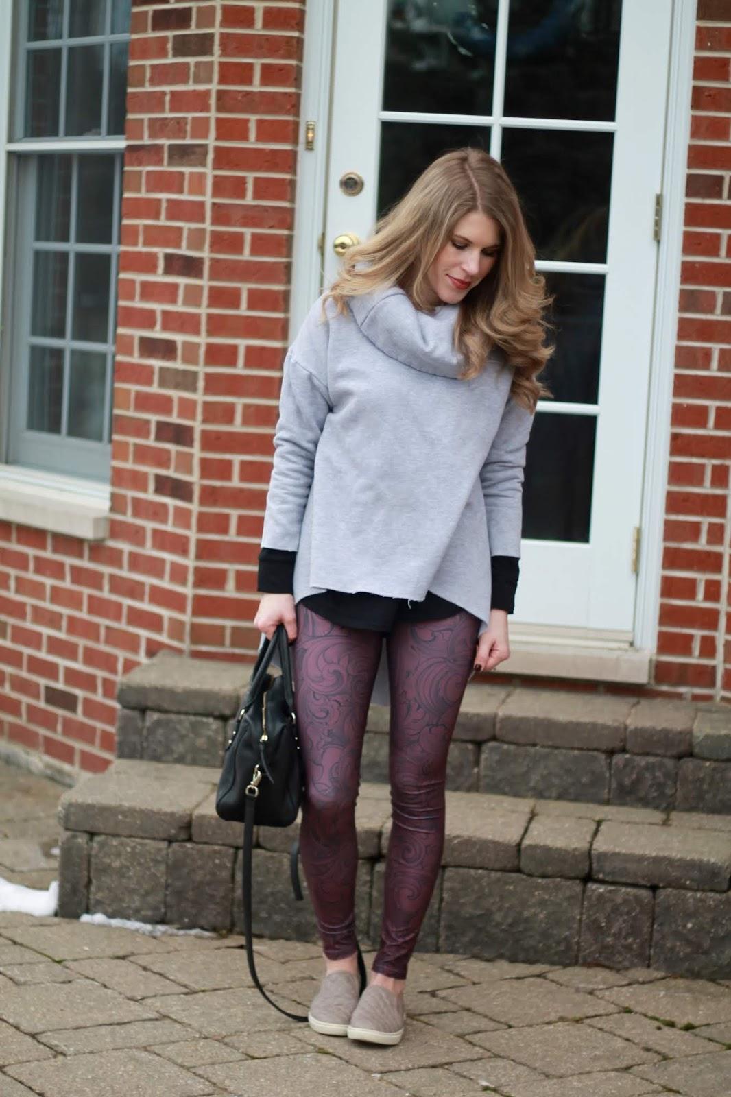 burgundy printed leggings, tunic sweatshirt, taupe slip ons, grey cable knit tunic, black booties, kate spade black crossbody bag, black floppy hat