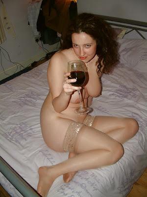 mulher nua em casa bebendo vinho