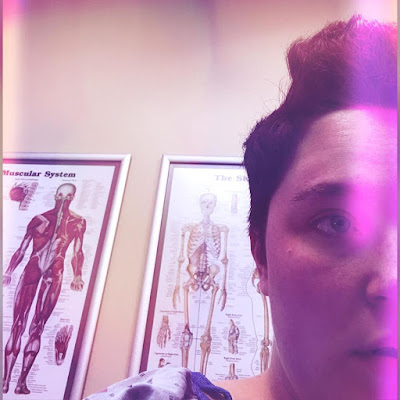 selfie of me with short hair; in the background are posters of the skeletal system and muscular system; I look tired/annoyed/run down and am wearing a hospital gown, though you only see a snippet of it on my right shoulder; there is a filter on this photo that makes it look distressed and discolored